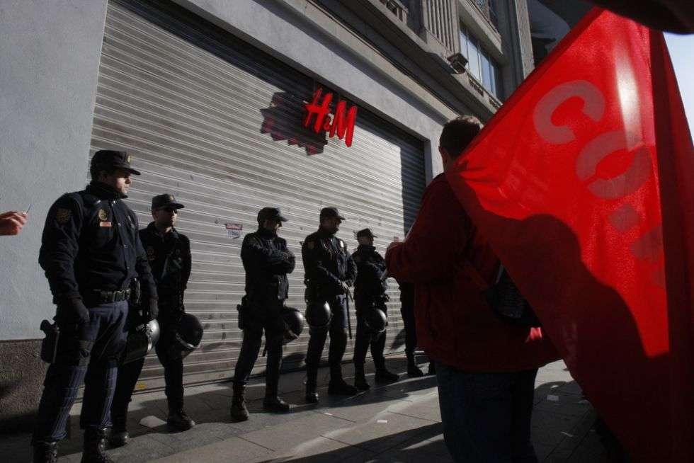 Policías antidisturbios vigilan una tienda en el centro de Madrid.